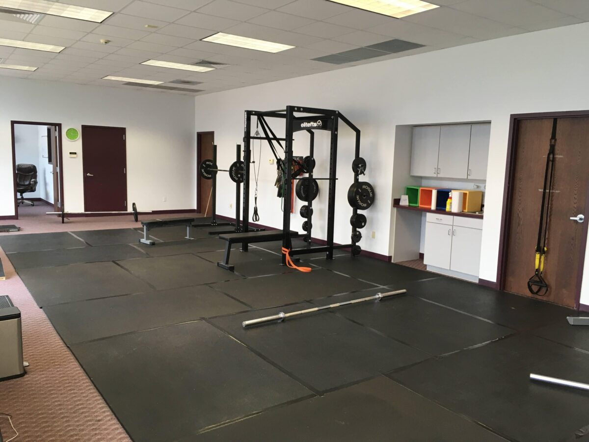Fitness Studio with stall mats laid out, squat rack and cubbies in the background