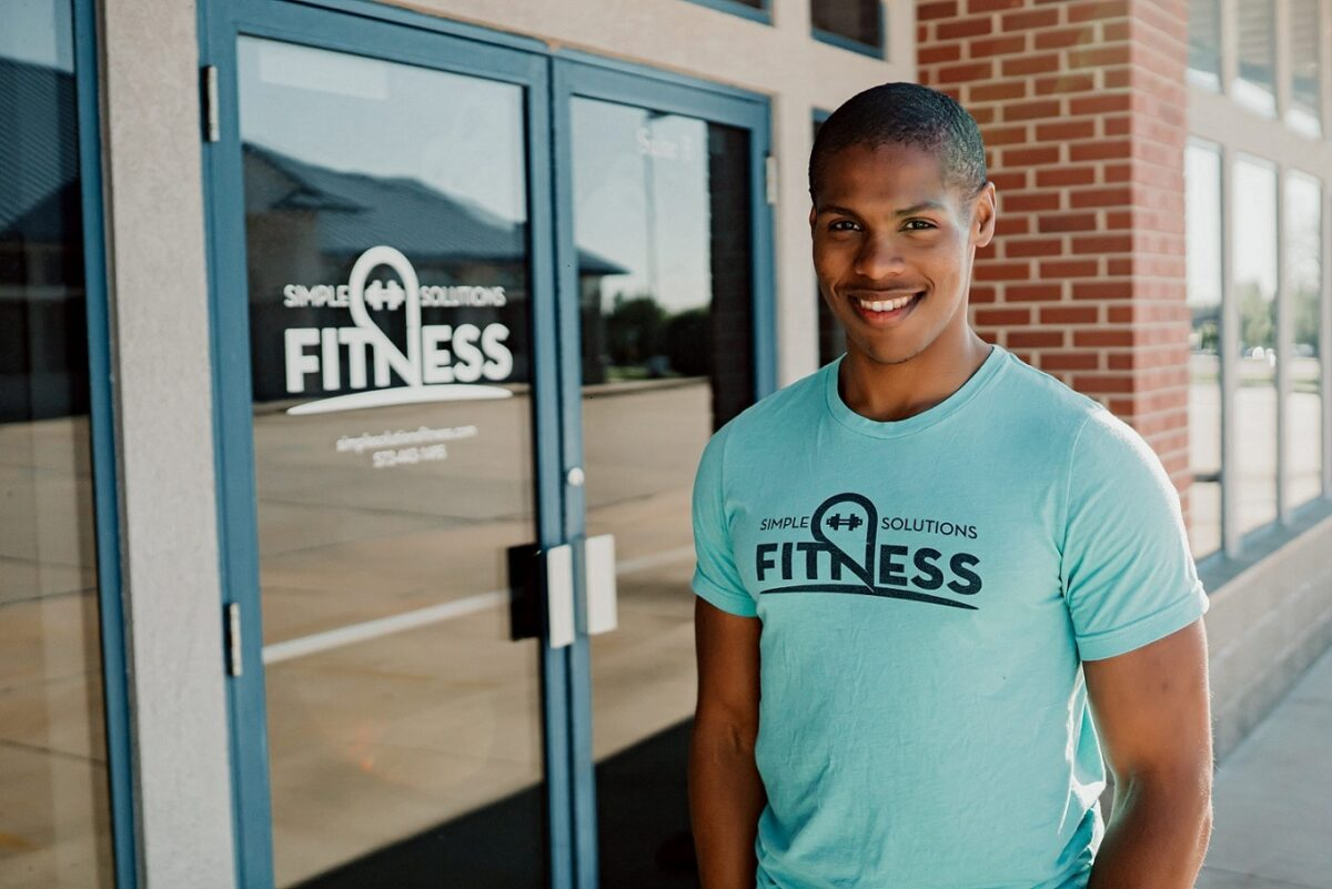 Personal Trainer Steven Mack Smiling in front of the Simple Solutions Fitness Studio in a blue logoed shirt