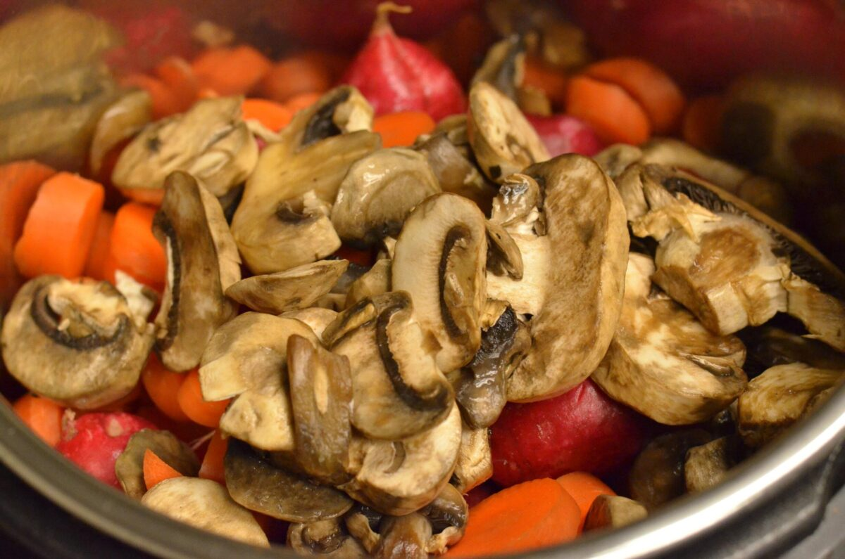 Sliced white mushrooms, carrots and radishes in a silver, metal pot