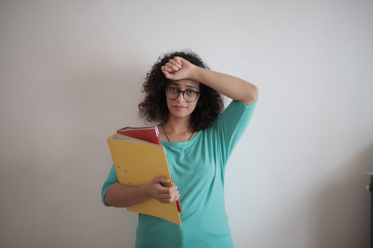 Stressed woman wearing glasses with folders in her arms