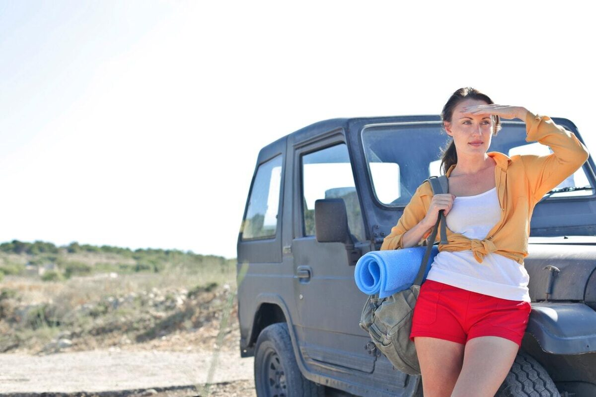 Woman in white shirt with bag over her shoulder blocking the sun from her eyes as she stands next to a weather jeep staring off into the distance