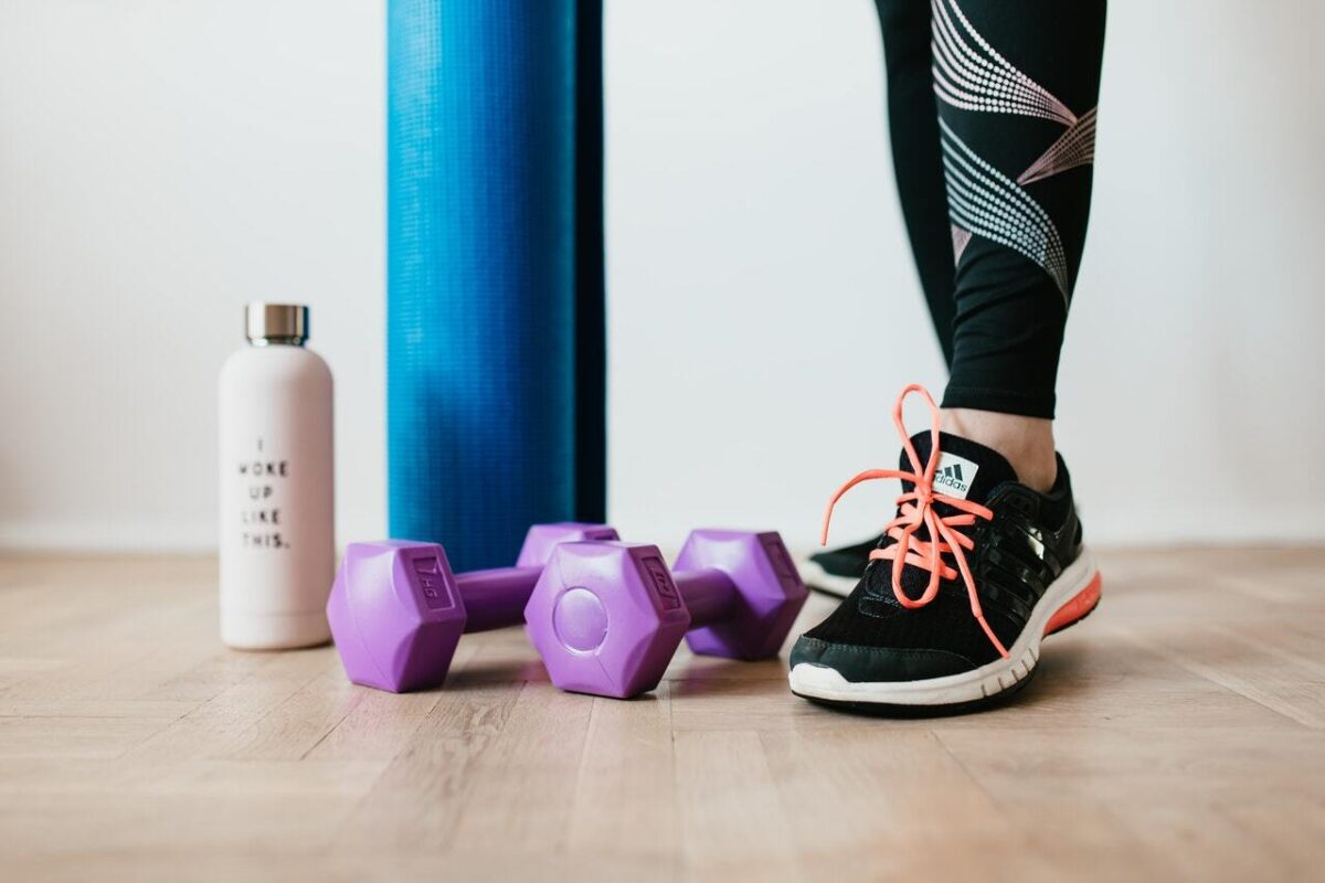Woman standing in black adidas shoes next to a blue yoga mat purple dumbbells and a water bottle