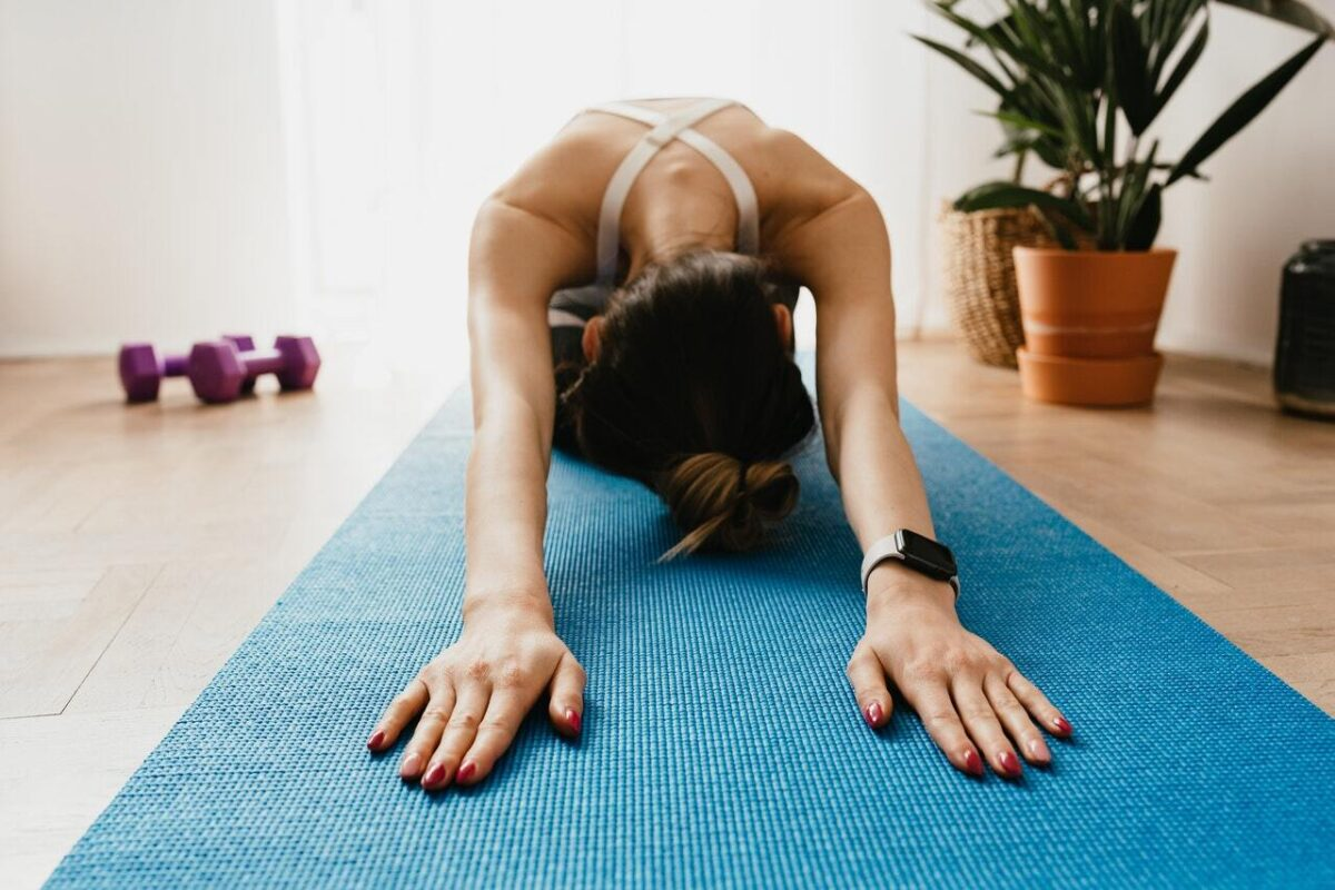 Woman stretching on a blue yoga mat with dumbbells lying just out of focus behind her