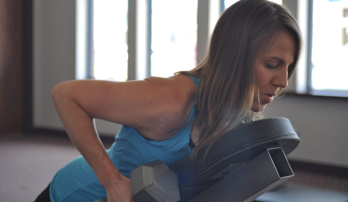 Kayla Performing a dumbbell row on an adjustable bench