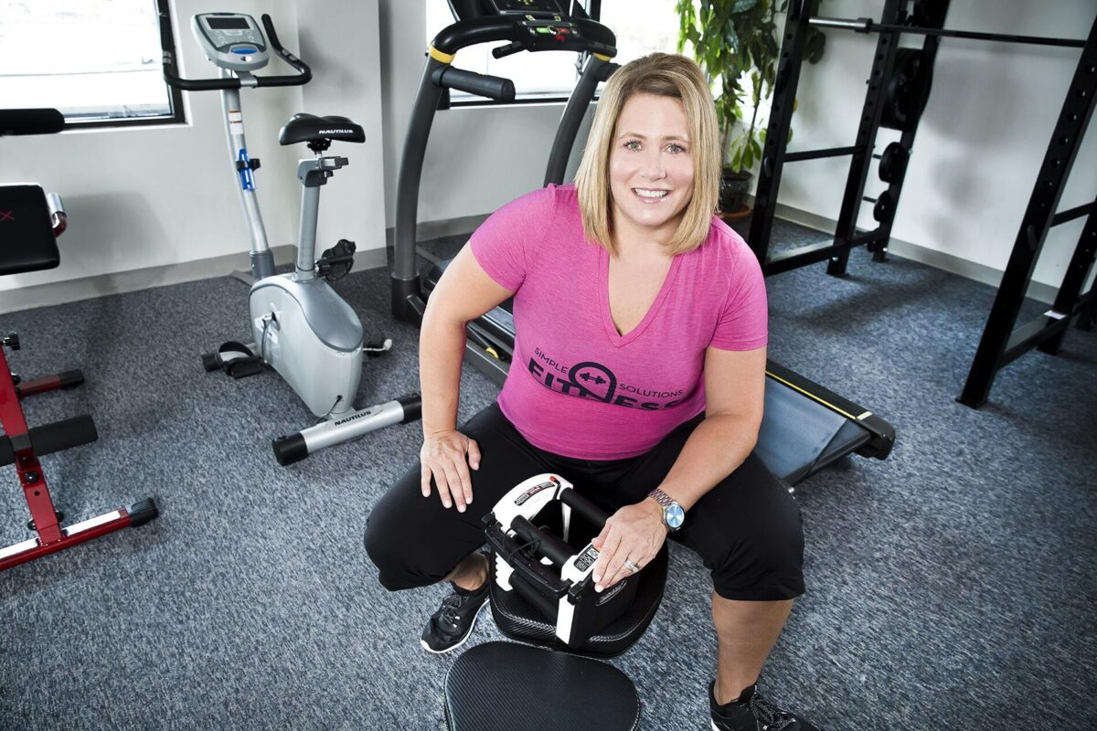 Client rebecca smiling and posing on a fitness bench