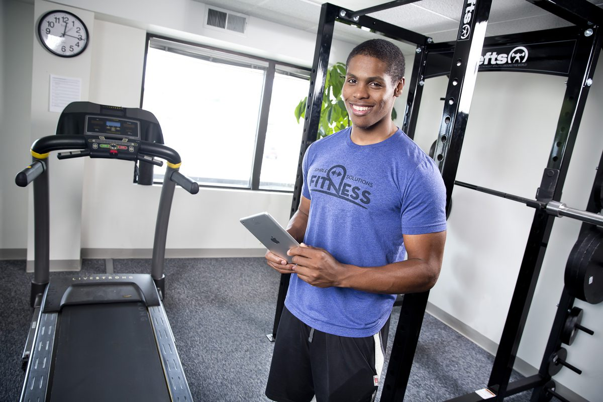 Personal Trainer Steven Mack Smiling, Wearing a Dark Blue Shirt